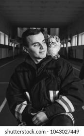 the fireman is holding a kitten