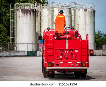 fireman on Firefighter truck under danger situation all firemen wearing suit for safety at oil refinery background