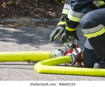 Fireman operating the valve of a firehose
