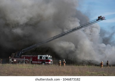 Fireman spraying water on a brush fire from the end of a hook and ladder