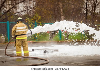 Fireman in uniform put out the fire with foam