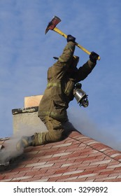 Fireman using a ax to break through the roof of a burning house.