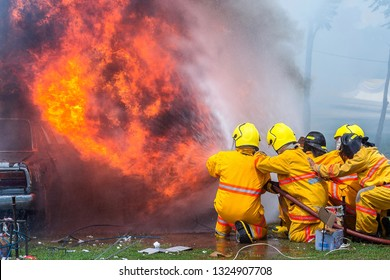 fireman using water and extinguisher car is on fire,Firefighter using extinguisher and water from hose for fire fighting,burning car Gas.