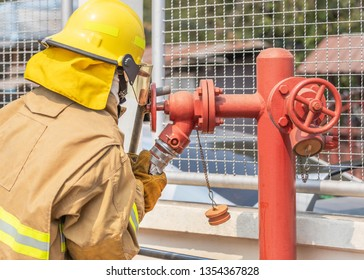 Fireman in yellow fire fighter uniform during connect firehose tube in to fire hydrant
