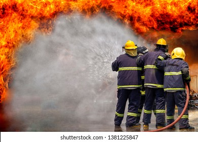 Fireman,fireman using water and extinguisher to fighting with fire flame in an emergency situation., under danger situation all firemen wearing fire fighter suit for safety.