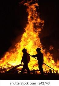 Firemen control a bonfire.