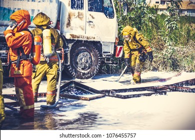 Firemen in firefighter uniform during fire drill and training for safety with foam and chemical fire suppression systems. Backside is fuel tanker truck. Vintage tone.