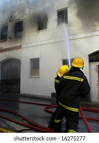 Firemen putting out fire in old building