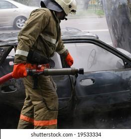 Firemen struggling against burning car