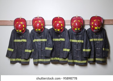 Firemen suits and helmets hanging inside a room