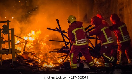 Firemen at work in uniform in from of the fire putting the rests of a burning falla sculpture made of paper at Las Fallas festival in Cullera, Valencia, Spain.