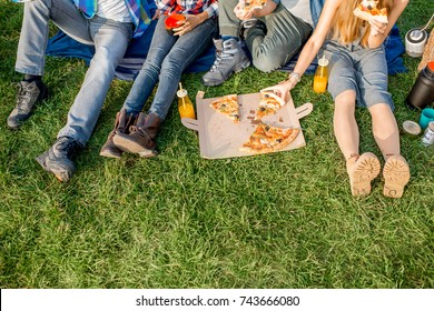 Firends eating pizza sitting on the grass. View from above on the legs and pizza