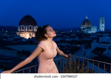 Firenze or Florence, Italy historic city with famous architecture church duomo in summer evening sunset night cityscape skyline and young woman girl on rooftop looking up