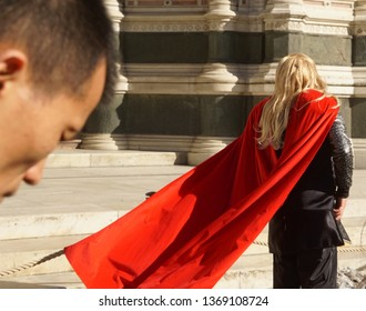 Firenze, Florence / Italy - March 16 2019: During the Firenze Fantasy Festival, a cosplayer dressed by Thor is waiting in front of an ancient building. The wind moves his red cape.