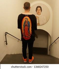 Firenze, Florence / Italy - September 28 2018: During Marina Abramovic solo show in Firenze, a man wearing a sweater with a Madonna print is looking at Marina Abramovic photo on the wall.