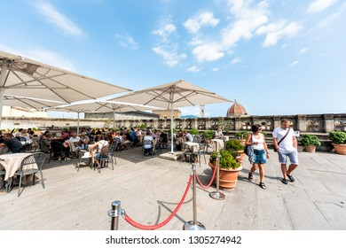 Firenze, Italy - August 30, 2018: Many people by cafe on terrace of famous Florence Uffizi art museum gallery with view of old building church duomo