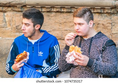 Firenze, Italy, October 12, 2017: Two young guys eat fast food on the street