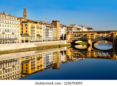 Firenze, Italy - October 30, 2014: Panoramic view of the Arno River and stone medieval bridge Ponte Vecchio with beautiful reflection of colorful houses, Florence, Tuscany, Italy.
