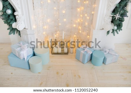 fireplace with blue and white christmas decorations with present boxes with ribbons and light bulbs inside