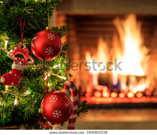 Fireplace burning, christmas time. Cozy warm home, xmas tree decorated, wood logs fire glowing in the dark.