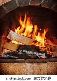 Fireplace with burning firewood. Firewood in the hearth