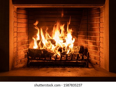 Fireplace burning with firewood logs. Christmas, winter, and travel concept. Warm cozy home