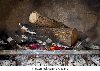 fireplace with burning wood logs on iron grate and ash