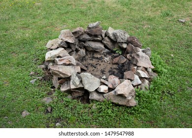 Fireplace and campfire ring - stones and ashes. Green grass around camp fire.