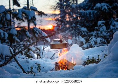 Fireplace and coffee pot in Finland. There is a sunset in the background. There is a lot of snow and frost.