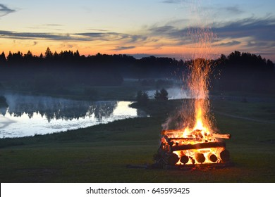 Fireplace hipe and stack and midsummer festival fire flames on the hill near the lake at sunny summer evening