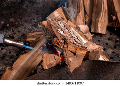 Fireplace kindling of chopped wood logs by gas torch. Method of firing at camping outdoor. Close up image of burning woods and flamethrower head