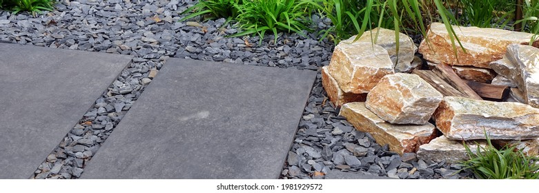Fireplace from Limestone in Designed Alpine Backyard Garden with Tiled Footpath. Stone Fire Pit from Stone with Firewood near Garden Path from Tiles and Gravel. Landscaped Backyard Design.