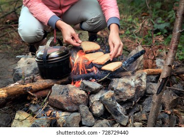 fireplace made from stones, campfire, firewood, kettle, and bread on the grid. Female hands on the background
