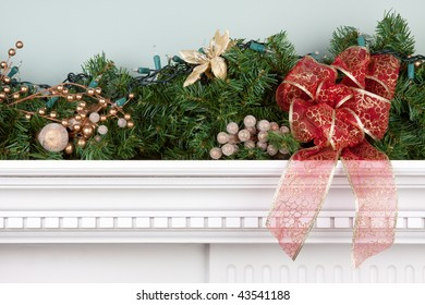 A fireplace mantle is decorated for Christmas with garland, lights, a bow and other decorations.