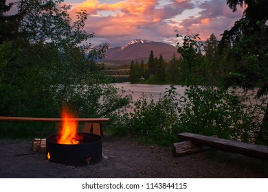 A fireplace near a beautiful river in the mountains. The sun in the background is setting. A lovely scenery.