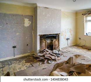 Fireplace removed from the chimney breast, carpets and underlay pulled up and piled in the centre of the room, walls stripped bare. A full do it yourself (DIY) renovation project.