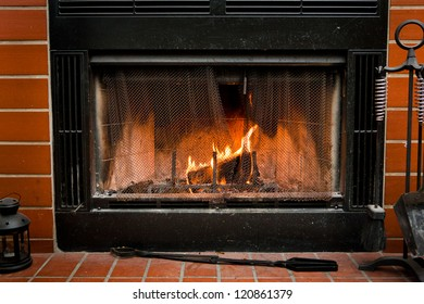A fireplace surrounded by red brick, with a fire burning inside of it.
