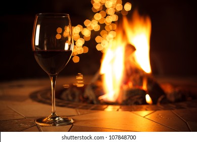 Fireside with a Glass of Wine - A relaxing environment near the fire, enjoying a glass of red wine with some bokeh lights in the background.