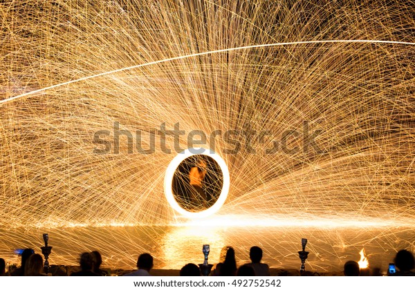 """Firestarter performing amazing fire show with sparkles in the night .Koh Pha Ngan,Thailand.well known as original """"Full Moon Party"""" Island."""
