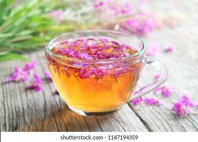 Fireweed healthy herbal tea. Mug of chamerion tea and bunch of medicinal herbs on background, not in focus.