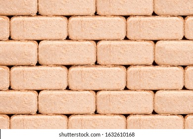 Firewood briquettes stacked on top of each other. Background of wooden briquettes for ignition. Wall of briquettes. A lot of briquettes for lighting a fire.