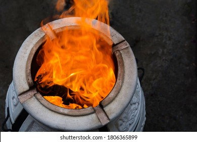 Firewood is burned in a tandoor heating it before cooking meat. Evening in the garden. Tandoor  is a special spherical or pitcher-shaped grill or roaster made of clay for cooking various food