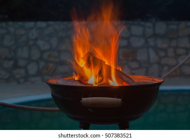Firewood burning in grill bowl at night