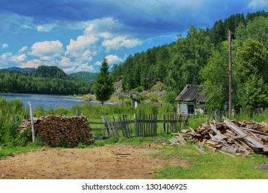 Firewood at the fence and an old wooden rural house on the banks of the Biya River in the Altai Republic in Russia