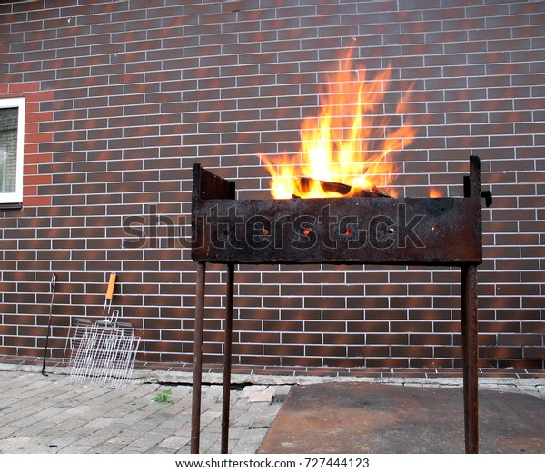 Firewood and fire in the old rusty charcoal grill on brick wall background