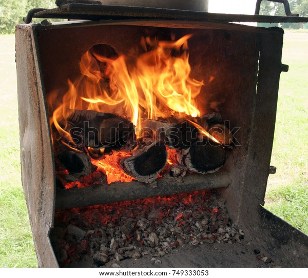 Firewood and fire in the old rusty charcoal grill