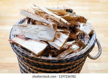 Firewood for a fireplace for heating a house during the cold season in a wicker basket in the living room.