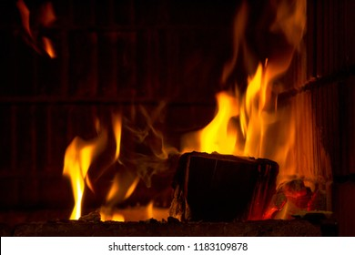 Firewood in flames and smoke of the fireplace background