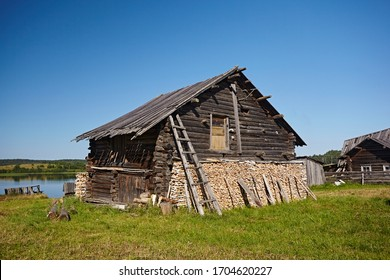 A firewood at the old wooden house against the blue sky in the village