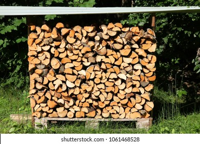 Firewood outdoor storage - covered wooden logs stacked.